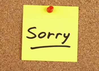 sorry sticky note on bulletin board